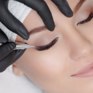 Cosmetologist making permanent makeup, close up. Tattooist making permanent make-up. Attractive lady getting facial care and tattoo. Permanent make-up tattoo at beauty salon